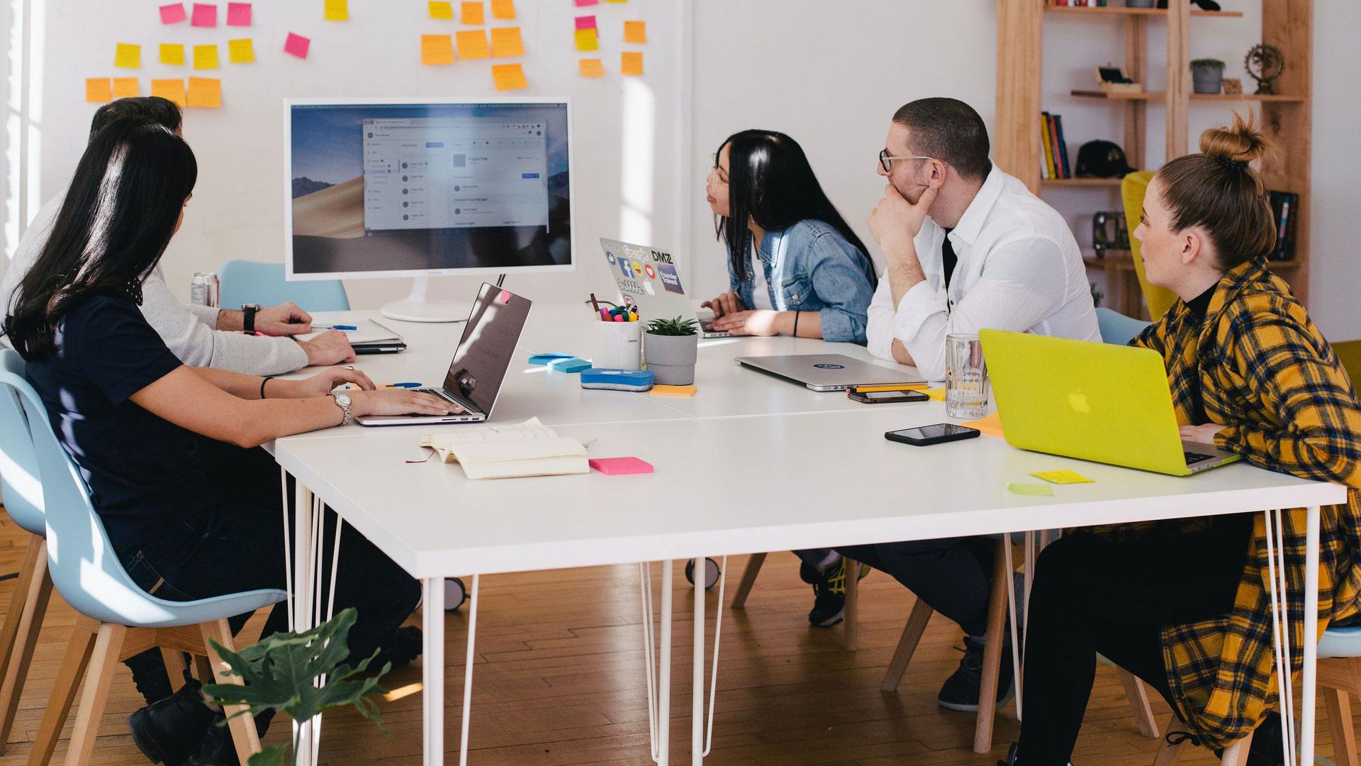 pessoas em reunião a olhar para um ecrã de computador
