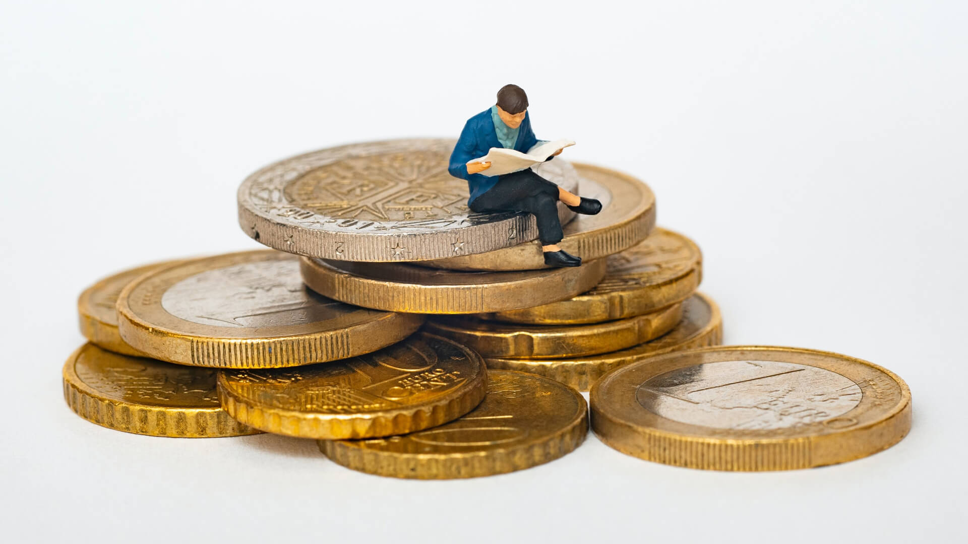 boneco sentado em moedas