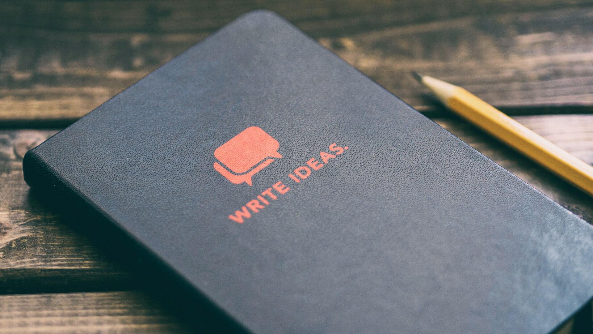 bloco de notas e lápis em cima de mesa de madeira