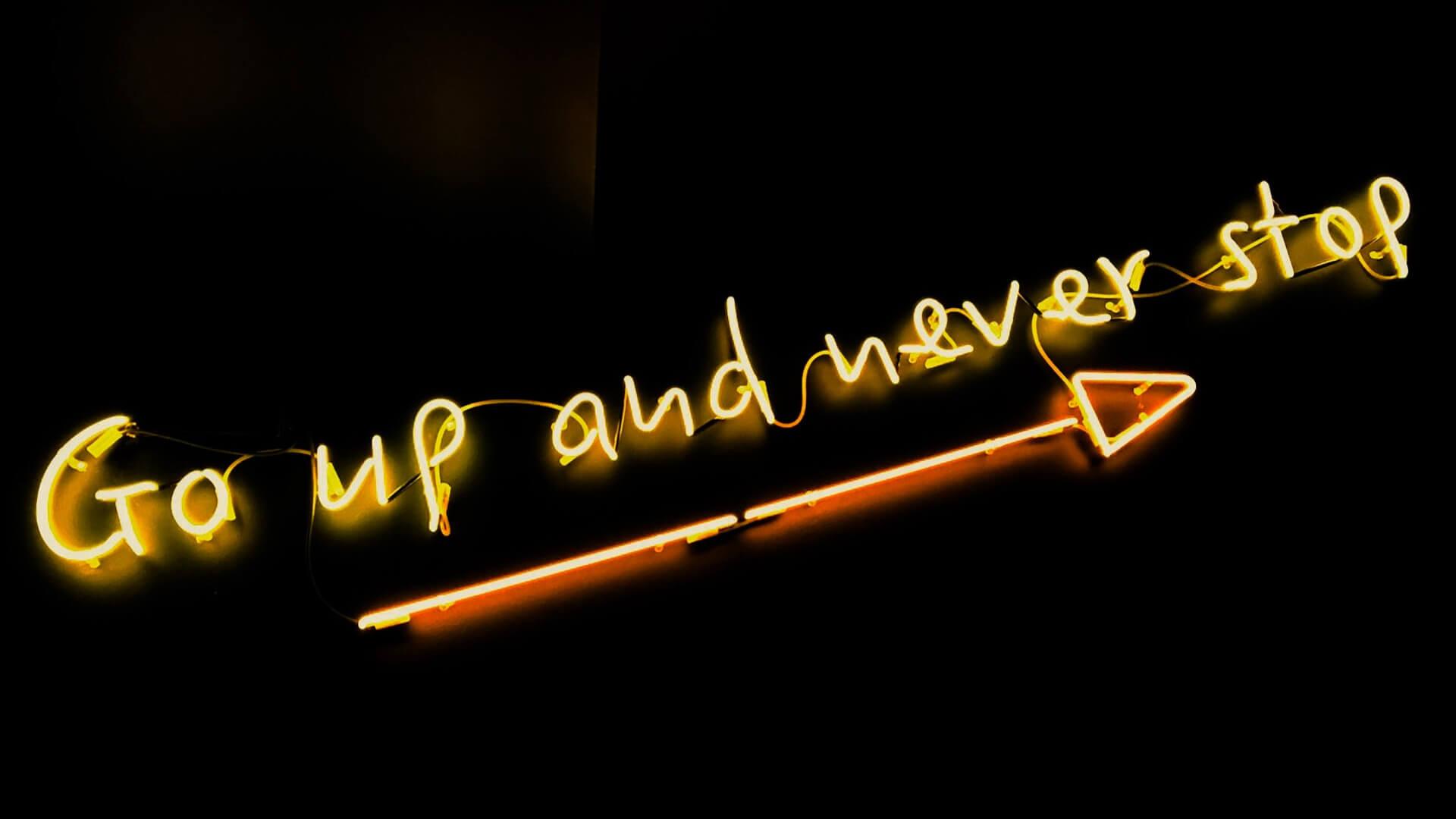 Neon com as palavras Go up and never stop