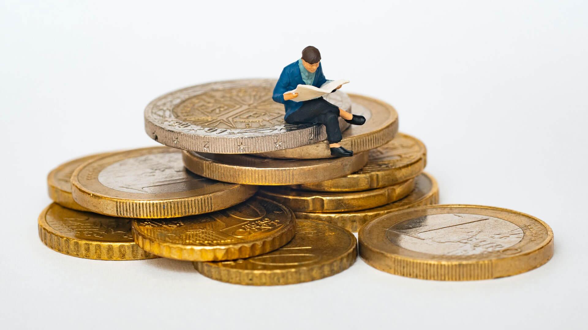 Boneco sentado em moedas de euro