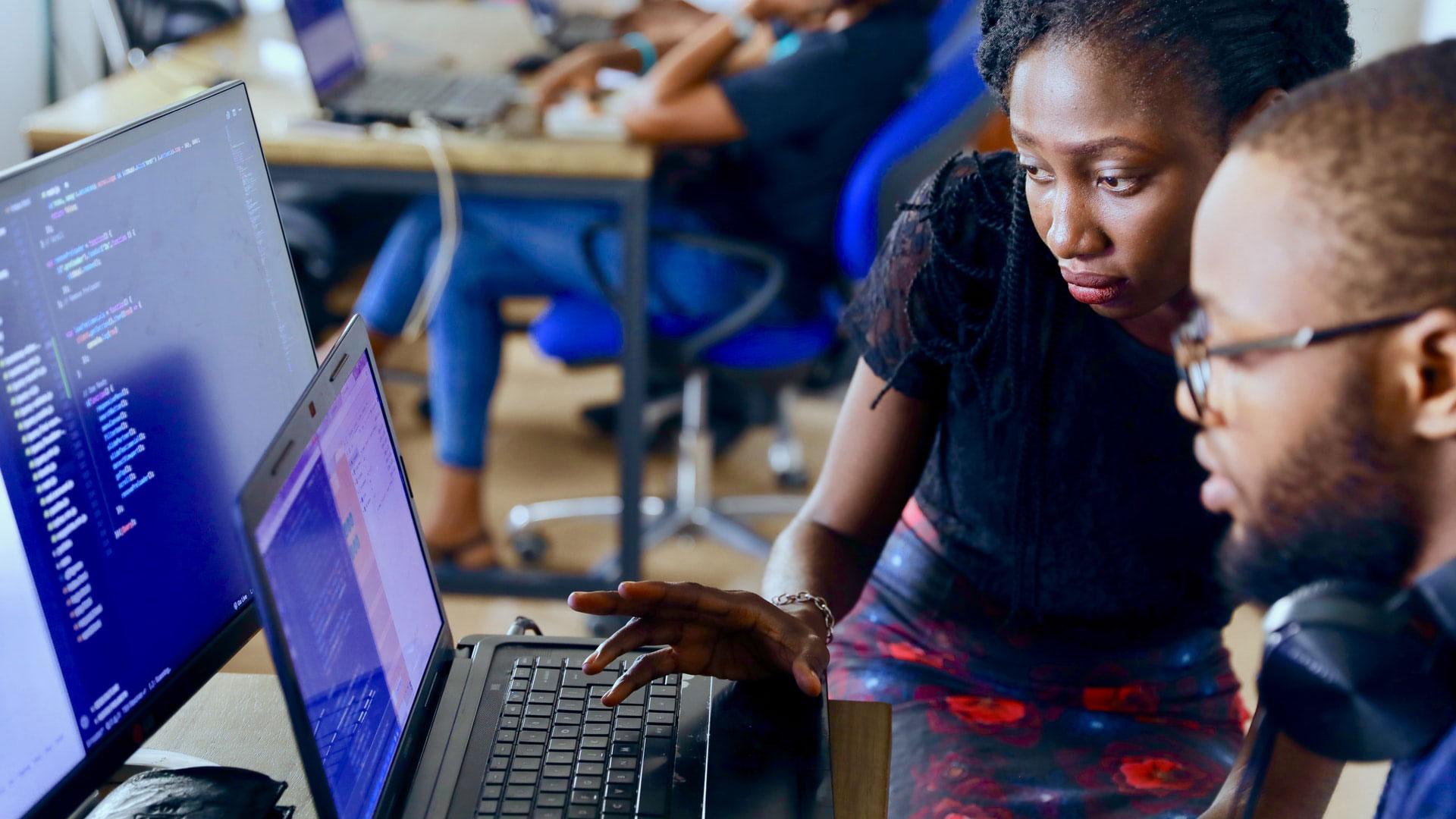 duas pessoas a olhar ecrã de computador